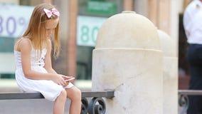 Ni?a adorable con el tel?fono m?vil en el d?a caliente al aire libre en ciudad europea cerca de Fontana famoso di Trevi metrajes