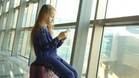 Ni?a adorable en aeropuerto cerca de la ventana grande que juega con su tel?fono almacen de metraje de vídeo