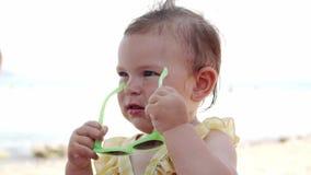 Ni?a con las gafas de sol en la playa en el centro tur?stico Ni?o divertido Viaje con un bebé Playa del verano almacen de metraje de vídeo
