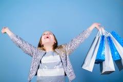 Ni?a con los paquetes del manojo Etiqueta estacional de sale Cliente de la muchacha de la moda Ni?o feliz en tienda con los bolso imagenes de archivo