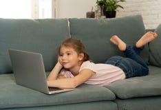 Ni?a encantadora linda hermosa que juega y que practica surf Internet en el ordenador port?til que sonr?e en casa foto de archivo libre de regalías