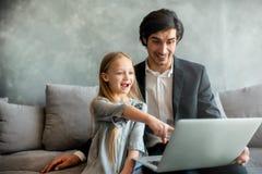 Ni?a feliz que mira una pel?cula en el ordenador con su padre fotos de archivo libres de regalías