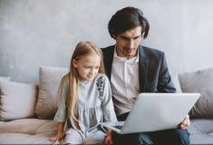 Ni?a feliz que mira una pel?cula en el ordenador con su padre foto de archivo libre de regalías