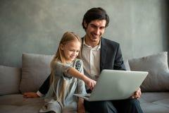 Ni?a feliz que mira una pel?cula en el ordenador con su padre imágenes de archivo libres de regalías