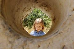 Ni?a fotografiada en el c?rculo de piedra de una muela verde oliva en Italia La muchacha est? pensando fotos de archivo