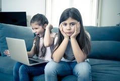 Ni?a joven que usa el ordenador port?til que ignora su viejo solo triste enojado fotografía de archivo