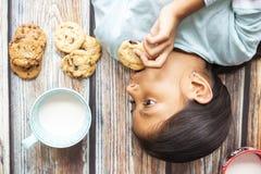 Ni?a linda que come las galletas con leche imagenes de archivo