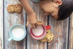 Ni?a linda que come las galletas con leche imagen de archivo