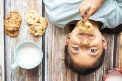 Ni?a linda que come las galletas con leche fotos de archivo libres de regalías