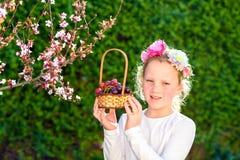Ni?a linda que presenta con la fruta fresca en el jard?n soleado Ni?a con la cesta de uvas fotografía de archivo