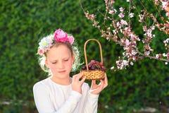 Ni?a linda que presenta con la fruta fresca en el jard?n soleado Ni?a con la cesta de uvas imagenes de archivo