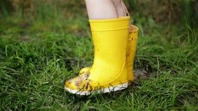 Ni?a linda que salta en el charco fangoso que lleva los guardapolvos de goma amarillos Ni?ez feliz almacen de video