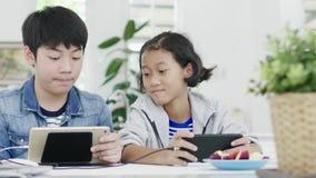 Ni?a linda y muchacho joven que juegan en videojuego competitivo en smartphones y la tableta, almacen de video