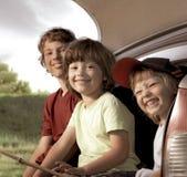 Ni?o alegre tres que se sienta en el tronco de un coche en la naturaleza imagen de archivo