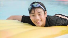 Ni?o asi?tico feliz que juega en piscina con la cara de la sonrisa