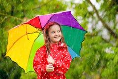 Ni?o con el paraguas que juega en lluvia del verano foto de archivo libre de regalías