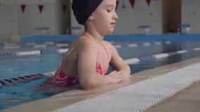 Ni?o de la muchacha en piscina El ni?o lleva una forma de vida sana y afilado sonrientes en deportes almacen de video