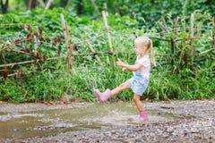 Ni?o en las botas de goma rosadas bajo la lluvia que saltan en charcos Ni?o que juega en parque del verano Diversi?n al aire libr fotografía de archivo