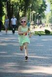 Ni?o feliz que corre en parque de la ciudad Ni?a que disfruta de funcionamiento imagen de archivo