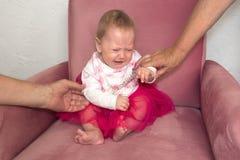 Ni?o gritador Histeria del ni?o Emociones negativas del ni?o, ni?o Beb? que se sienta en la silla en vestido rosado imagenes de archivo
