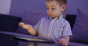 Ni?o lindo que entretiene con la tableta Little Boy que pasa el tiempo libre que juega al juego m?vil en y machaca el brillante almacen de metraje de vídeo