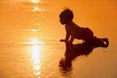 Ni?o peque?o en la playa del mar de la puesta del sol foto de archivo