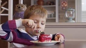 Ni?o peque?o encantador que come la baya de una torta que miente en una placa en un caf? almacen de video
