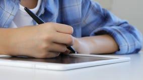 Ni?o que estudia en la tableta, muchacha que escribe en la clase de escuela, aprendiendo haciendo la preparaci?n metrajes