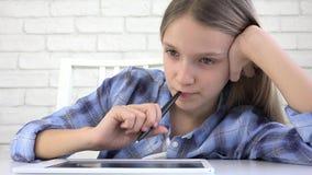 Ni?o que estudia en la tableta, muchacha que escribe en la clase de escuela, aprendiendo haciendo la preparaci?n almacen de metraje de vídeo