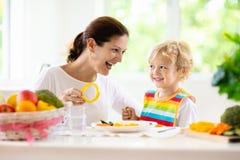 Ni?o que introduce de la madre La mam? alimenta verduras del ni?o fotografía de archivo