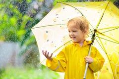 Ni?o que juega en la lluvia Cabrito con el paraguas foto de archivo libre de regalías