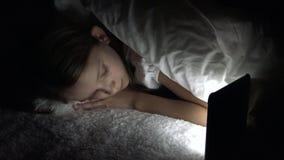Ni?o que juega la tableta en la noche oscura, Internet de la ojeada de la muchacha en la cama, no durmiendo almacen de video