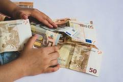 Ni?o que recoge la pila de billetes de banco euro de diverso valor imagenes de archivo