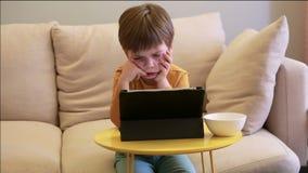 Ni?o que usa la PC de la tableta en cama en casa El muchacho lindo en el sof? est? mirando la historieta, est? jugando a juegos y almacen de video