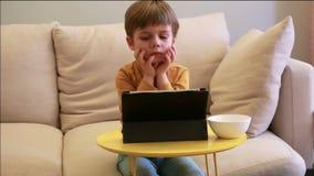 Ni?o que usa la PC de la tableta en cama en casa El muchacho lindo en el sof? est? mirando la historieta, est? jugando a juegos y metrajes
