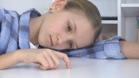 Ni?o triste, muchacha aburrida que juega los fingeres en el escritorio, ni?o infeliz subrayado que no estudia fotografía de archivo libre de regalías