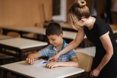 Ni?os de ayuda de la escuela del profesor que escriben la prueba en sala de clase educación, escuela primaria, aprendizaje y conc fotos de archivo