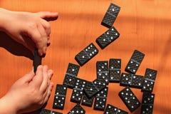 Ni?os de ense?anza para jugar al juego de los domin?s en un fondo de madera imagenes de archivo