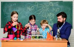 ni?os en capa del laboratorio que aprenden qu?mica en laboratorio de la escuela Laboratorio de qu?mica profesor feliz de los ni?o fotografía de archivo