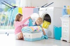 Ni?os en lavadero con la lavadora fotos de archivo libres de regalías