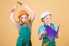 Ni?os felices Carrera futura peque?as muchachas que reparan junto en taller El D?a del Trabajo 1 puede Ni?os en casco con imagen de archivo libre de regalías