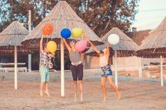 Ni?os felices con los globos del color que saltan en la playa arenosa fotos de archivo