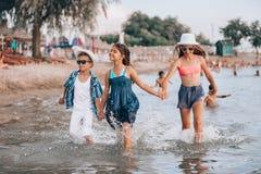 Ni?os felices que corren junto a trav?s del agua y que llevan a cabo las manos imagen de archivo