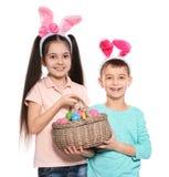 Ni?os lindos en las vendas de los o?dos del conejito que sostienen la cesta con los huevos de Pascua en blanco imagenes de archivo