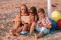 Ni?os que juegan con la tableta digital en la playa arenosa imagenes de archivo