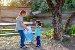 Ni?os que limpian en parque Ni?os voluntarios con un bolso de basura que limpia la litera, poniendo la botella pl?stica en el rec foto de archivo