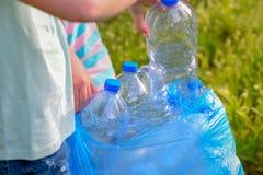 Ni?os que limpian en parque Ni?os voluntarios con un bolso de basura que limpia la litera, poniendo la botella pl?stica en el rec foto de archivo libre de regalías