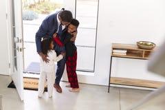 Ni?os que saludan y que abrazan el hogar de trabajo de As He Returns del padre del hombre de negocios del trabajo imagen de archivo