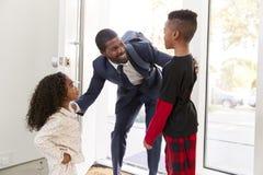 Ni?os que saludan y que abrazan el hogar de trabajo de As He Returns del padre del hombre de negocios del trabajo imagen de archivo libre de regalías