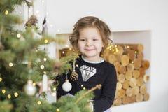Ni?a que adorna el ?rbol de navidad Navidad A?o Nuevo Muchos ornamentos y regalos del d?a de fiesta holiday indoor foto de archivo libre de regalías